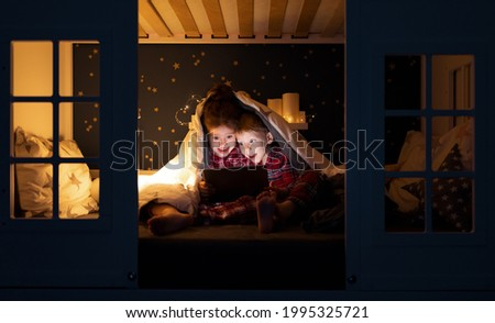 Happy boy and girl sitting under blanket and watching cartoon on tablet on comfortable illuminated bed at night at home Royalty-Free Stock Photo #1995325721