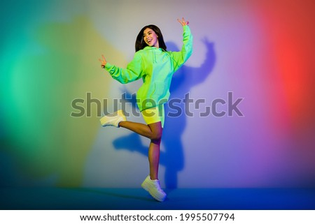 Full length body size view of beautiful trendy cheerful girl jumping showing v-sign isolated over multicolor vivid neon light background Royalty-Free Stock Photo #1995507794