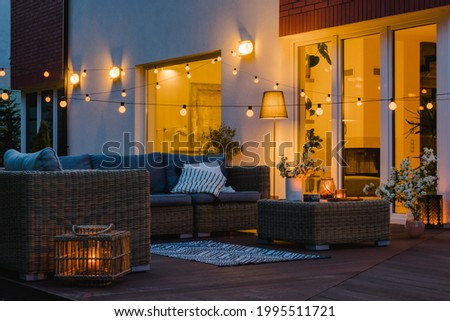Summer evening on the patio of beautiful suburban house with garden Royalty-Free Stock Photo #1995511721