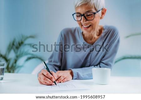 Senior woman solving sudoku puzzle game. Cognitive enhancement therapy for seniors.