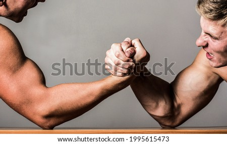 Arm wrestling. Two men arm wrestling. Rivalry, closeup of male arm wrestling. Two hands. Men measuring forces, arms. Hand wrestling, compete. Hands or arms of man. Muscular hand.