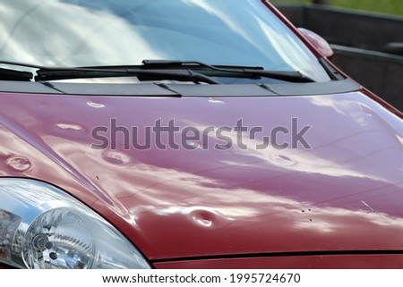 Hail damage at car, red colored car Royalty-Free Stock Photo #1995724670