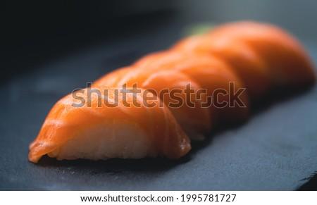 Salmon Sushi delicious in Japanese buffet restaurant.Fresh salmon fillet on black plate salmon slices.Asian people eating sashimi set Japan restaurant.salmon sashimi.Asian Food Menu.seafood sashimi.