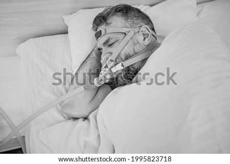 Monochrome portrait of Sleeping man with chronic breathing issues considers using CPAP machine in bed. Healthcare, Obstructive sleep apnea therapy, CPAP, snoring concept Royalty-Free Stock Photo #1995823718