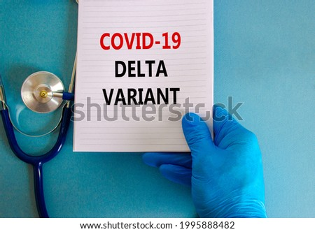 Covid-19 delta variant strain symbol. Doctor hand in blue glove with white card. Concept words 'Covid-19 delta variant'. Stethoscope. Medical and COVID-19 delta variant strain concept. Copy space.