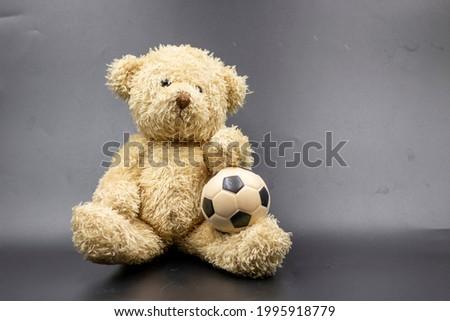 Teddy bear with soccer ball on black background.