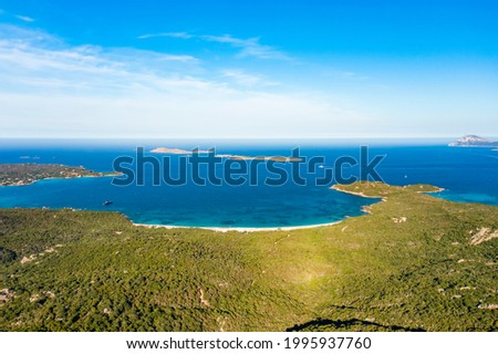 View from above, stunning aerial view of a green coastline with some beaches bathed by a turquoise sea. Liscia Ruja, Costa Smeralda, Sardinia, Italy.  Royalty-Free Stock Photo #1995937760