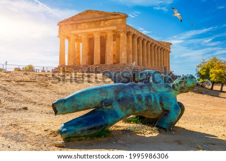 Bronze statue of Icarus in front of the Temple of Concordia at the Valley of the Temples. Temple of Concordia and the statue of Fallen Icarus, in the Valley of the Temples, Agrigento, Sicily, Italy. Royalty-Free Stock Photo #1995986306