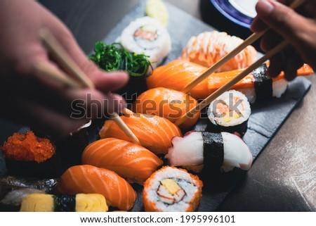 Salmon Sashimi in Japanese buffet restaurant menu.Fresh salmon sushi.Asian friends people using chopsticks  eating sashimi sushi set Japan in restaurant.Asian Food Menu.seafood sashimi.People and food