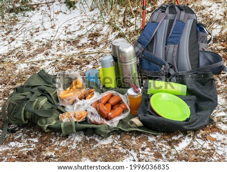 picture with snowy ground background and picnic accessories, backpacks, mugs, thermos and various dishes on the ground, tourist lunch at nature in winter