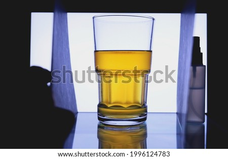 Behind the shooting process of glass of lager beer. Object photography at home. Shooting photo of beer on the background of white laptop screen. Home photography. Amateur photo. Home shooting scene.