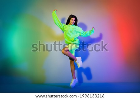 Full length body size view of attractive cheerful girl jumping having fun isolated over multicolor vivid neon light background Royalty-Free Stock Photo #1996133216
