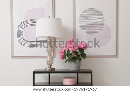 Console table with beautiful hydrangea flower and lamp near white wall in hallway. Interior design