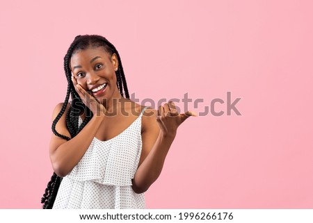 Joyful black lady pointing at blank space, touching her face in excitement over pink studio background. Charming African American woman advertising your product, promoting sale or discount Royalty-Free Stock Photo #1996266176