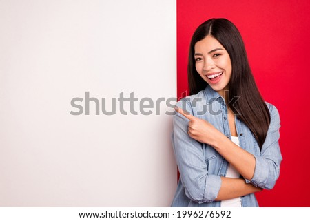 Portrait of lovely trendy cheerful girl demonstrating big board advert novelty message isolated over bright red color background Royalty-Free Stock Photo #1996276592