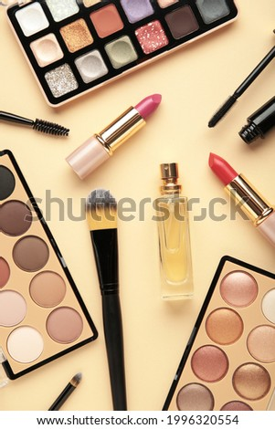 Set of decorative cosmetics on beige background. Vertical photo. Top view