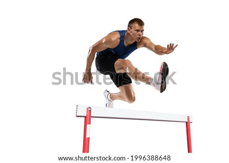 Caucasian professional male athlete jumping over the barrier isolated on white background. Running with obstacles concept. Muscular man. Action, motion, healthy, sport and lifestyle. Copyspace for ad. Royalty-Free Stock Photo #1996388648