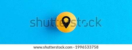 Map geo pin location icon on yellow ball on blue background.