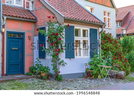 Charming garden with roses,two chairs,table.Old house in the background.Idyllic summer day in countryside. Royalty-Free Stock Photo #1996548848