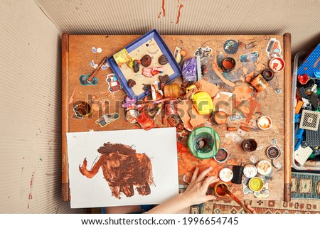 Little kid hand draws picture of elephant with brown paint at messy wooden table with dirty jars and toys close upper view