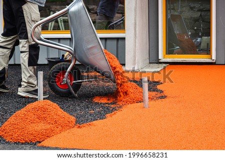 Side work. Construction side work. making a floor with the rubber beads on playground, New childrens playground under construction.  Flooring with the soft rubber bead. Royalty-Free Stock Photo #1996658231