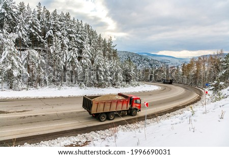 A truck is driving on a winter forest road. Winter forest road truck. Truck on snowy winter road. Winter snowy truck trip Royalty-Free Stock Photo #1996690031