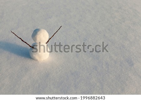one small snowman in the winter season, the snowman is made of several parts and stands in the snow in cold weather, snow games with the creation of one snowman figure Royalty-Free Stock Photo #1996882643