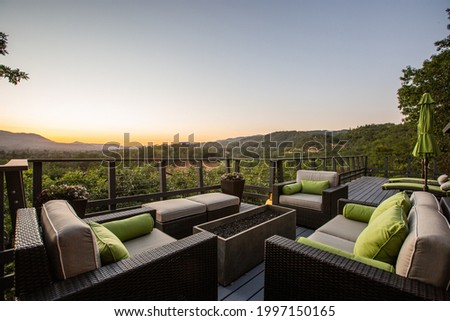 Twilight from the Deck of a Wine Country Home, Relaxing Couches Face Sunset over the Mountain Royalty-Free Stock Photo #1997150165