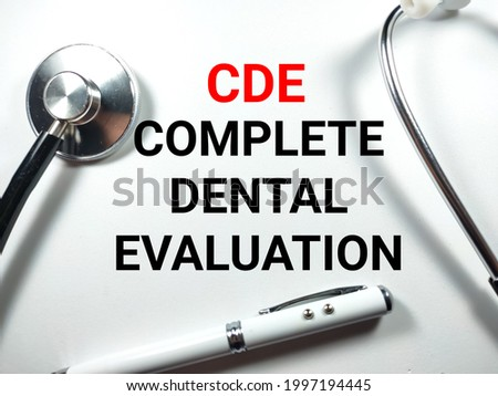 Medical concept.Text CDE (Complete Dental Evaluation) with pen and stethoscope on white background