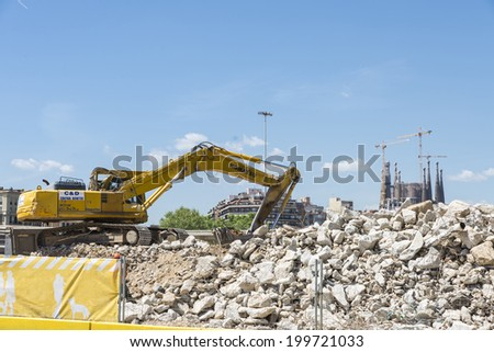 Barcelona, Spain - 28 April, 2014: excavator placing sand or debris on a truck with the Sagrada Familia in the background.  #199721033
