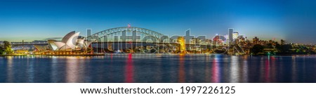 Panoramic night view of Sydney Harbour and City Skyline of NSW Australia bright neon lights reflecting off the water