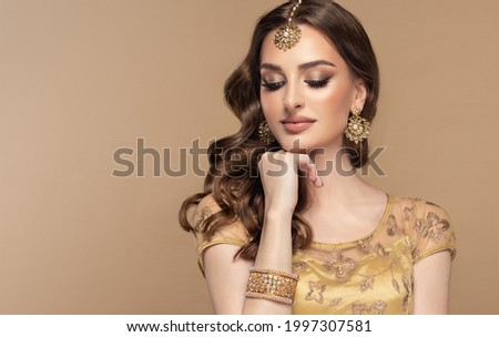 Portrait of beautiful indian girl. Young hindu woman model with golden kundan jewelry set, earrings, tikka and bracelet  . Traditional India costume lehenga choli or saree . Curly hair