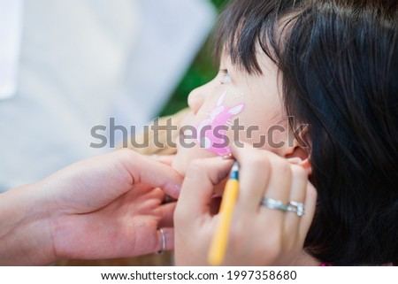 Asian girl sitting for painting face during Easter. An adult's hand is drawing a rabbit cartoon on a cute child face. Children 4-5 years old are engaged in Easter activities.