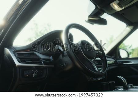 Black premium car interior. Dashboard, steering wheel, speedometer at sunny day Royalty-Free Stock Photo #1997457329