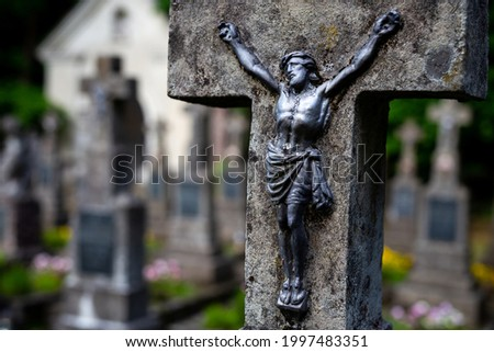 Jesus figurine on the cemetery cross. Picture taken in a soft light, shaded place.
