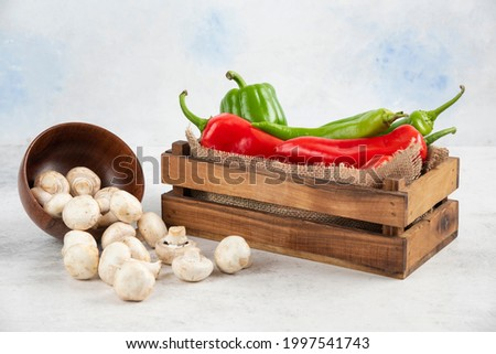 White mushrooms with red and green chili peppers in a wooden tray. High quality photo