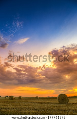 Sunset over farm field with hay bales #199761878