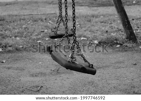 Ruined seats of an old abandoned swing. Black and white photo of an old abandoned playground. Melancholy childhood memories. Seats hung with chains ruined by time.