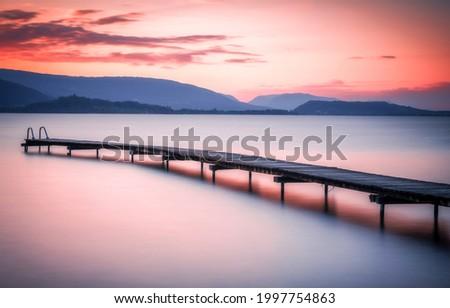 Sunset over the mountain lake pier. Sunset lake pier. Lake pier at sunset. Mountain lake pier at sunset Royalty-Free Stock Photo #1997754863