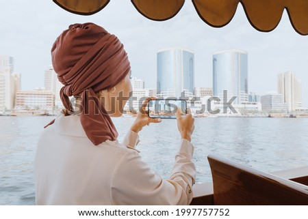Happy asian woman in a red turban takes pictures on her smartphone while cruising on a traditional Abra Dhow boat on Dubai Creek. Travel in UAE concept