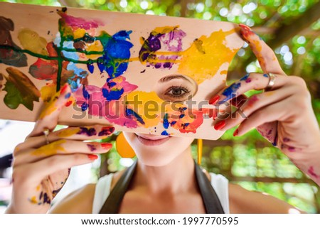 Playful portrait of a young gorgeous female artist painter covered in paint, looking and smiling at camera through her painter's palette. Creativity and individuality concept. Royalty-Free Stock Photo #1997770595