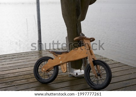 Old children's wooden bicycle in the rain. High quality photo Royalty-Free Stock Photo #1997777261