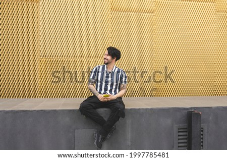 man with mobile and tattoos on golden background