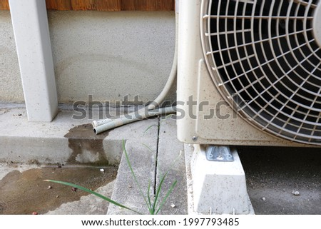 A drain hose that drains condensation water from an air conditioner. Royalty-Free Stock Photo #1997793485