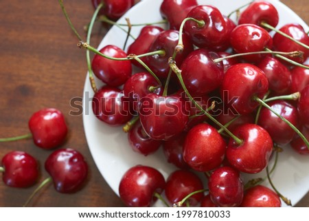 Fresh red cherries fruit on plate on wooden background close up. High quality photo Royalty-Free Stock Photo #1997810033