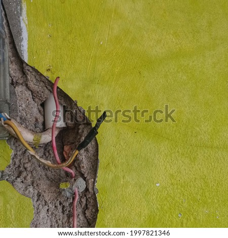 picture of cracked green wall with chipped wires and it is very dangerous