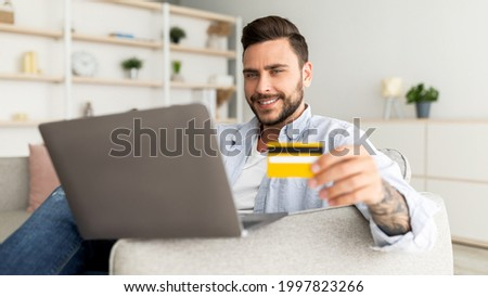 Online payment concept. Happy guy using laptop and credit card, sitting on comfy sofa. Young man shopping online, transferring money or booking vacation, panorama, copy space, closeup