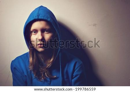 Sad teen girl in hood sitting #199786559