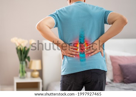 Lumbar spine hernia, man with back pain at home, compression injury of the intervertebral disc in the lower back, photo with highlighted skeleton Royalty-Free Stock Photo #1997927465