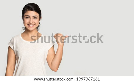 Portrait of smiling Indian woman isolated on grey studio background point at blank empty copy space. Happy millennial mixed race female show good promotion deal or sale discount. Commerce concept.